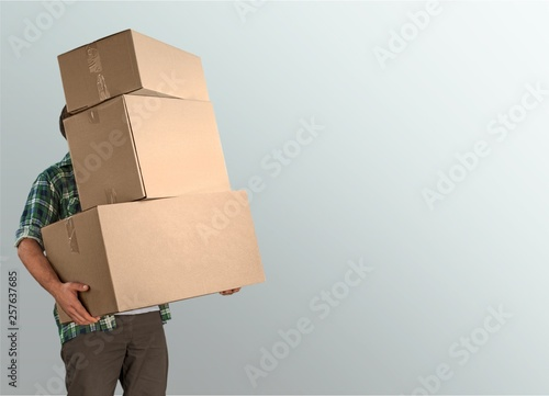 Obraz Delivery man carrying stacked boxes in front of face against  background - fototapety do salonu