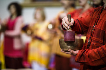 Man playing on a tibetian singing bowl (shallow DOF; color toned image)