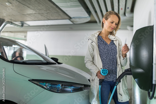 Fotografía Young woman charging an electric vehicle in an underground garage equiped with e-car charger