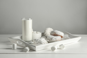 Fototapeta na wymiar Tray with tasty sweets and glass of milk on white table