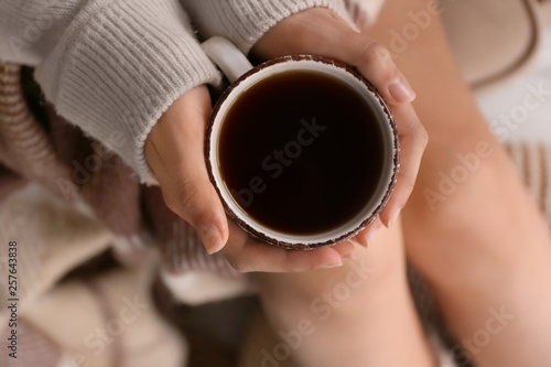 Tuinposter Thee Young woman drinking hot tea at home, closeup