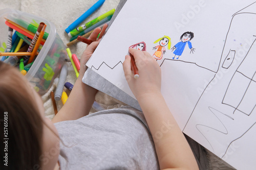 Photo Girl in bright clothing draws a picture of the family. Light room