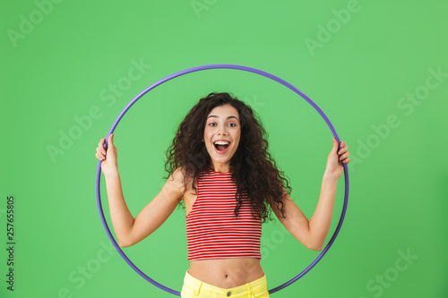 Fototapeta Photo of energetic woman 20s wearing summer clothes doing exercises with hula ho