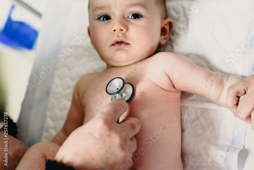Photo Sick baby examined by the doctor in a medical consultation, auscultated with a stethoscope
