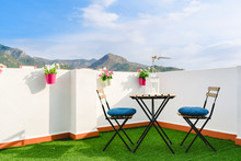 Beautiful White Terrace With Chairs And Coffee Table Overlooking The Mediterranean Mountain, Blue Sky.