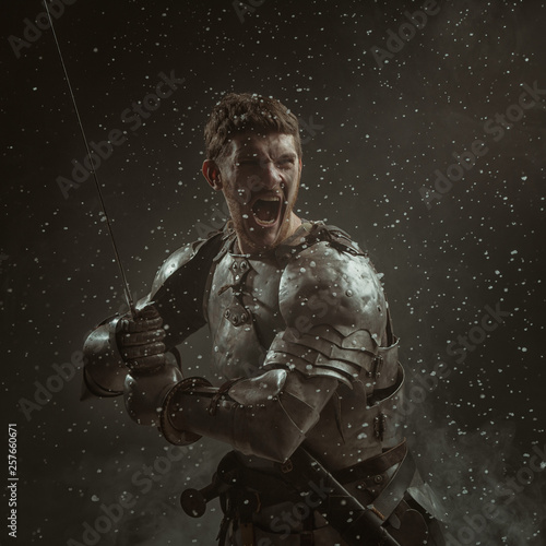Foto Emotional portrait of a young man in knight armor and a sword against a dark background