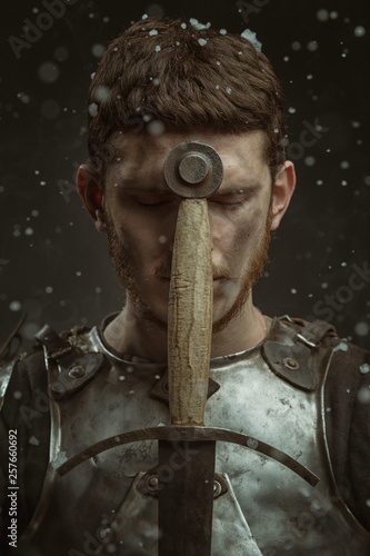 Fotomural Emotional portrait of a young man in knight armor and a sword against a dark background