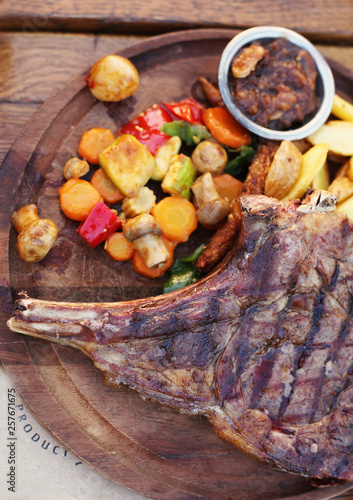 Aluminium Prints Grill / Barbecue Delicious dinner with Dallas steak with grilled vegetable on the side on a wooden serving board. Barbecue restaurant.