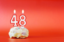 Forty Eight Years Birthday. Cupcake With White Burning Candle In The Form Of Number 48. Vivid Red Background With Copy Space