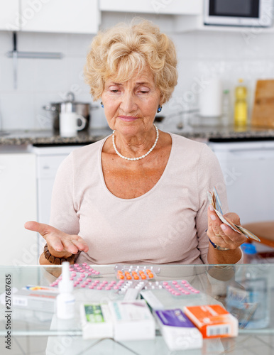 Obraz Woman counting her expenditure on medicines - fototapety do salonu