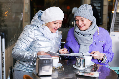Photo  Senior females reading city map in outdoors cafe