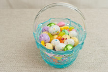 Top, Front View Of An Artisan, Blue, Glass Easter Basket, Filled With Easter Candy, Jelly Beans, Candy Eggs