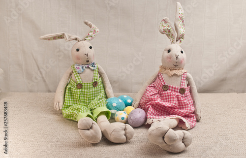 Front view, medium distance of two stuffed easter rabbits, in checkered pants, with easter eggs