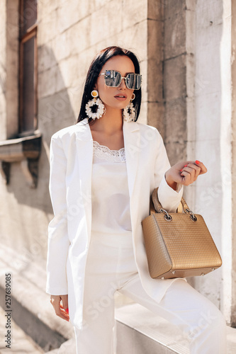 beautiful woman with dark hair in elegant white suit and coat, with accessories