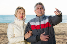 Mature Couple Walks Outdoors And Point By Hand