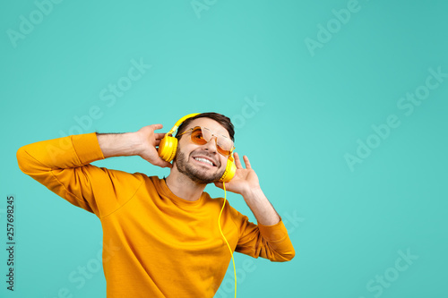 Foto  Handsome bearded young man wearing yellow sunglasses listening to music with yellow headphones on cyan background