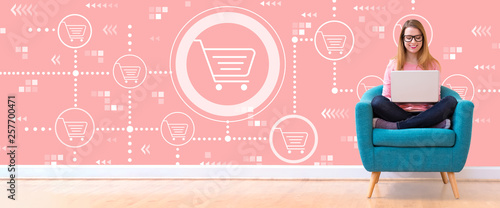 Valokuva Online shopping theme with young woman using her laptop in a chair