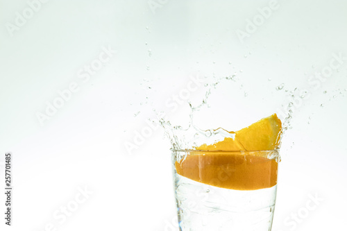 Fotografie, Obraz  Slice the orange slice in a glass of water and make a spray on a white background