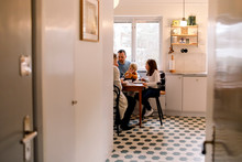 Family Having Meal Together In Kitchen At Home