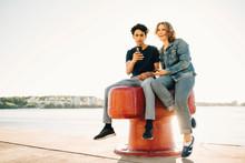 Two Teenage Boys Sitting On Bollard With Smartphone