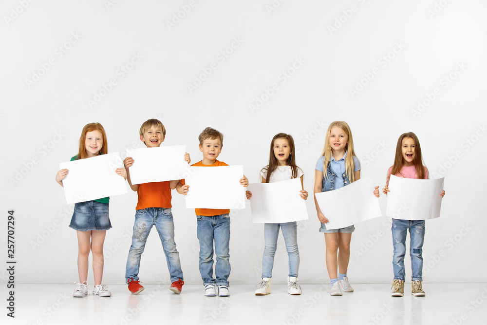 Fototapety, obrazy: Group of happy smiling children with a white empty banners isolated in white studio background. Education and advertising concept