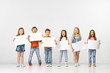 canvas print picture - Group of happy smiling children with a white empty banners isolated in white studio background. Education and advertising concept