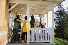 Happy Mature Men Embracing While Standing On Porch By Friends