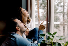Father And Daughter Looking Through Window At Home