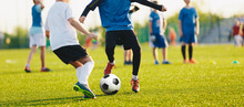 Boy Kicking Soccer Ball. Close Up Action Of Boys Soccer Teams, Aged 8-10, Playing A Football Match