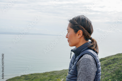 Young sporty Asian woman looking out at the beautiful ocean view. Young woman hiker standing admiring the view. healthy active lifestyle concept