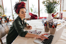 Young Beautiful Woman With Dark Curly Hair Sitting At The Table Dreamily Using Laptop And Drawing Sketches Spending Time In Modern Workshop With Big Windows
