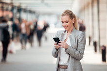 Beautiful Smiling Businesswoman Using Smartphone On The City Street.