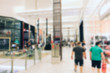 Defocused shopping mall background. Abstract blur and bokeh beautiful luxury shopping mall indoor with crowd of people