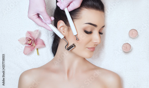 Valokuva  The cosmetologist makes the apparatus a procedure of Microcurrent therapy of a beautiful, young woman in a beauty salon
