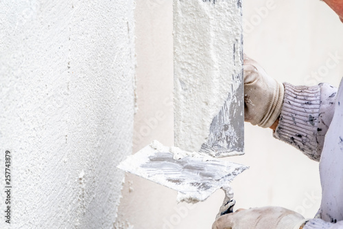 Fotomural  Construction worker plastering and smoothing concrete wall with cement