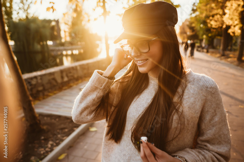 Beautiful young girl listening to music in the park through a wireless earpiece - 257744085