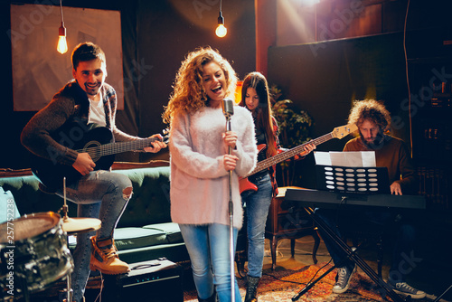 Band practice for the show. Woman with curly hair holding microphone and singing while man in background playing acoustic guitar. Home studio interior. - 257752238