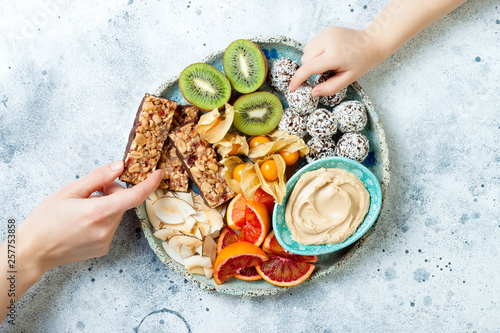 Fototapeta Mother sharing healthy vegan dessert snacks with toddler child. Healthy sweets for children. Protein granola bars, homemade raw energy balls, cashew butter, toasted coconut chips, fruits platter obraz