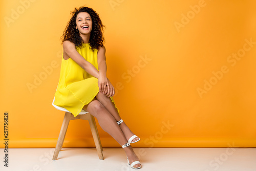 happy curly african american woman sitting in yellow dress on chair and smiling Canvas-taulu