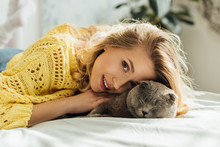 Beautiful Girl In Knitted Sweater Looking At Camera While Lying In Bed And Hugging Scottish Fold Cat