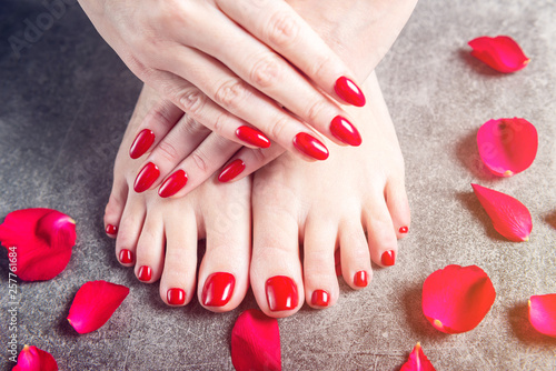 Young lady is showing her red manicure and pedicure nails Canvas-taulu