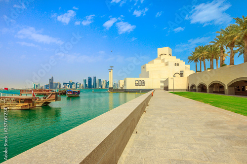 Fényképezés  Doha seafront with palm trees and West Bay skyline along Corniche in Qatari capital with Dhow Harbour in a sunny day