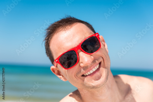 9d666dde55ba Closeup portrait of one happy smiling young man in red sunglasses standing  on beach in Florida