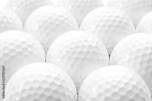 Valokuva  Brightly lit image of several golf balls creating a full frame pattern isolated