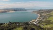 Aerial drone flying sideways away from Omapere, New Zealand. Beautiful town near river and hills.