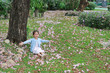 Smiling little Asian child girl sitting on green grass under tree trunk with falling pink flower in the park garden.