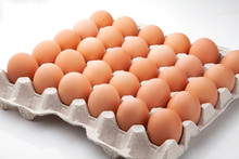 A Tray Of Yellow Homemade Chicken Eggs On A White Background.