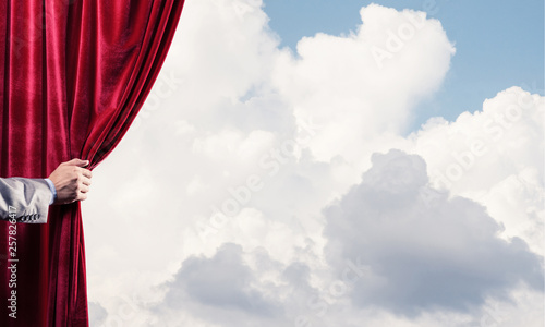 Aluminium Prints Heaven Cloudy landscape behind red curtain and hand holding it