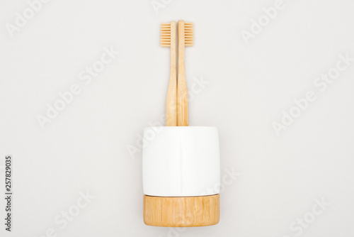 Stampa su Tela  bamboo toothbrushes in stand on grey background