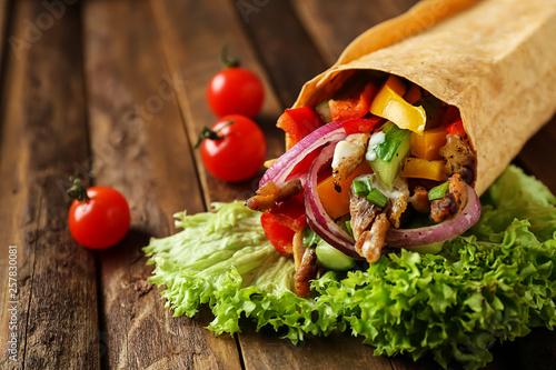 Tasty doner kebab on wooden table